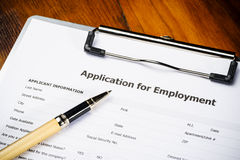 Job application. A job application on a clipboard with a pen Royalty Free Stock Photo