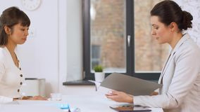 Employer having interview with employee at office. Job, business and employment concept - employer or hr manager having interview with asian female employee at stock footage