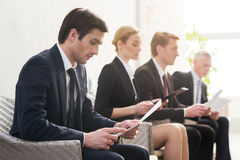 Job candidates. Four people in formalwear waiting in line while sitting at the chairs and holding papers in their hands Royalty Free Stock Photo