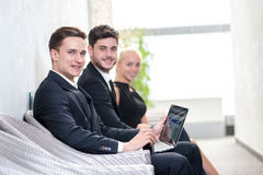 Job candidates. Three people in formalwear waiting in line while Stock Photo