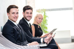 Job candidates. Three people in formalwear waiting in line while Royalty Free Stock Photo