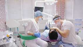 Job of a dentist is paired with a nurse in dental office over lying in a chair by patient. stock footage