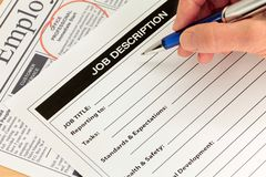 Job Description and Hand with Pen. Job Description with Hand and Pen and Newspaper Ad stock photo