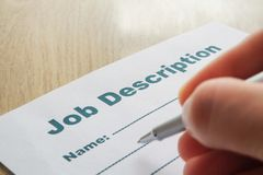 Job Description with Hand and Pen on the table. Job Description with Hand and Pen on the table close up stock photos