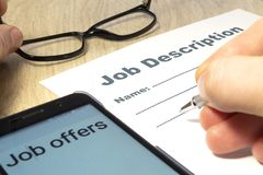 Job Description with Hand, smartphone and Pen on the table. Job Description with smartphone, Hand and Pen on the table close up royalty free stock photography