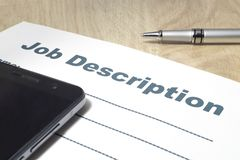 Job Description with smartphone and Pen on the table. Job Description with smartphone and Pen on the table close up stock photo