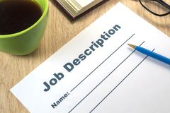 A job description template to fill out with pen and coffee. On the office desk close up stock image