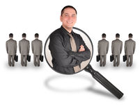Job Employee Man Candidate Search. A business man is smiling inside of a magnifying glass. There are other business men turned and standing. Use it for a job Royalty Free Stock Photos