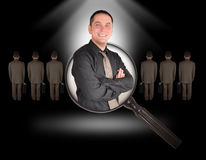 Job Employee Man Search on Black. A business man is smiling inside of a magnifying glass on a black background. There are other business men standing. Use it for Stock Photo