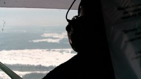 The job of a helicopter pilot in the cockpit in the winter. The job of a helicopter pilot of the aircraft in the cockpit in winter, flying over cities and stock footage