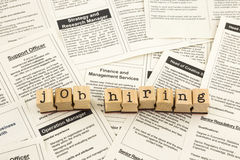 Job hiring. Word on wood stamps place on classifieds ads of newspapers stock photos