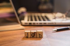Job hiring word on workplace. Cube wooden stamps with letters word Job on office table. Blur notebook, pen, glasses and books in background. Worldwide work at stock photography