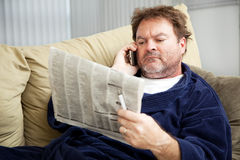 Job Hunt - Classified Ads. Unemployed man at home on the couch looking at the classified ads in the newspaper stock photos