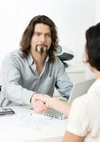 Job interview. Businessman shaking hands with applicant during job interview in office royalty free stock photography