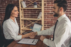 At the job interview. Beautiful employer and employee are shaking hands and smiling during the job interview stock photography