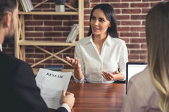 At the job interview. Beautiful female employee in suit is smiling during the job interview Stock Images