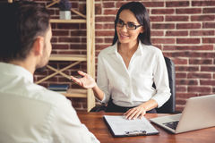 At the job interview. Beautiful female employer in suit is conducting a job interview while sitting in her office royalty free stock photography