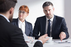 Job interview gives an opportunity to verify information about candidate. Recruiter indicates something in the papers of the candidate which is trying to explain royalty free stock photo