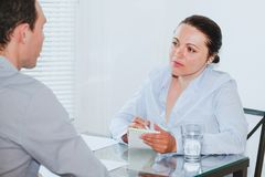 Job interview. In modern company office, strict women listening to young man Stock Images