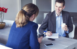 Job interview. Manager holding job interview with woman. Business meeting with coffee and cell phones on table stock photos