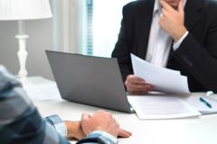 Job interview or meeting with bank worker in office. Business man considering. Discussion about loan, mortgage or insurance. Human resources conversation stock photo