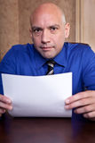 Job interview scrutiny. Interviewer holding a resume during an interview Royalty Free Stock Photos