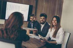 On a job interview. Young business women on a job interview offering her resume to a commission representative. Focus on the HR representative taking the resume stock image