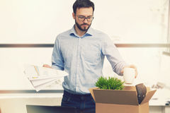 Job loss - fired man putting his belongings in cardboard box royalty free stock image