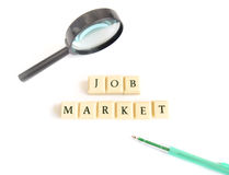 Job market. A concept photograph of the words job market spelt out in block letters, taken on clean white background with magnifying glass and green pen Royalty Free Stock Images