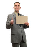 Job Market. A businessman hopeful about the job market holding a blank cardboard sign, isolated against a white background Royalty Free Stock Image