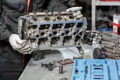 The job of a mechanic. Disassemble engine block vehicle. Motor capital repair. Sixteen valve and four cylinder. Car. Service concept Stock Images
