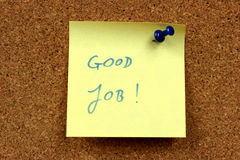 Job motivating. Yellow small sticky note on an office cork bulletin board. Good job - motivating and positive message Stock Photos