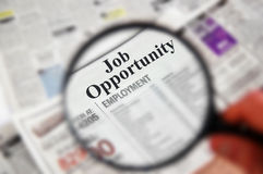 Job opportunity. Magnifying glass over a newspaper classified section with Job Opportunity text Stock Image