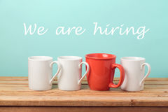Job recruit concept with coffee cups and text `We are hiring`. Business background. Job recruit concept with white and red coffee cups and text `We are hiring` royalty free stock image