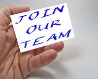 Job recruiting advertisement represented by `JOIN OUR TEAM` texts. On cards in man`s hands stock photography