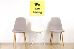 Head hunting help wanted poster concept. Minimalistic composition with chair and blank copy space wall. stock photos