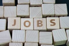 Job recruitment, career vacancy or hiring position in the company concept, cube wooden block with alphabet combine the word Jobs. On black background royalty free stock photography
