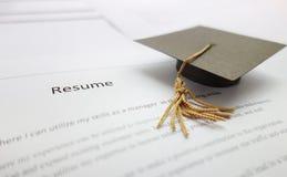 Job resume. Small graduation cap on a resume - recent college graduate concept stock images
