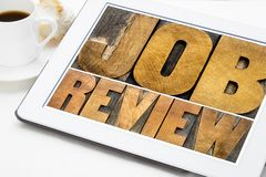 Job review word abstract in wood type. Job review - isolated word abstract in vintage letterpress wood type on a digital tablet with a cup of coffee stock photos