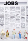 Job search. Miniature figurine of people standing in front of jobs  seeking offerings Royalty Free Stock Photos