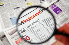 Job search. Magnifying glass over a newspaper classified section - jobsearch Royalty Free Stock Images