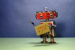Job search advert. Unemployed red robot wants to get a job. Funny toy robot with a cardboard sign and handwritten text royalty free stock images