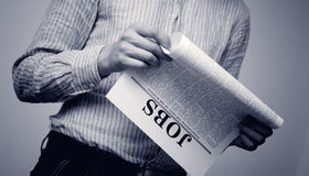 Job searching. Man seek for a job in a newspaper Stock Photography