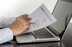 Job seeker review his resume on his desk with pen and computer l. Businessman or job seeker review his resume on his desk with pen and computer laptop Royalty Free Stock Images