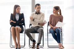 Job seekers compete for position, rivalry and competition betwee. Male and female ambitious job seekers waiting for interview, looking at each other with hate royalty free stock images