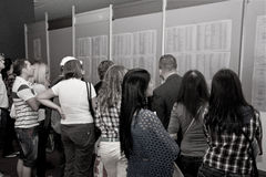Job-seekers queuing at the Jobs Fair for Graduates. The grim reality of the Great Recession: job-seekers queuing to read the lists of available job openings royalty free stock photography