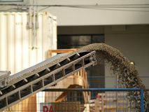 Job site delivery. Conveyor belt delivering cement mix to a job site Royalty Free Stock Image