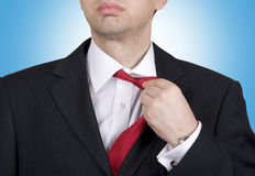Job stress. Young Businessman adjusting his tie Royalty Free Stock Image