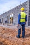 Job Supervisor Looks Over Building-Projekt Lizenzfreie Stockfotos