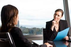 Job talk in business office. Two businesswomen in an office talking stock image